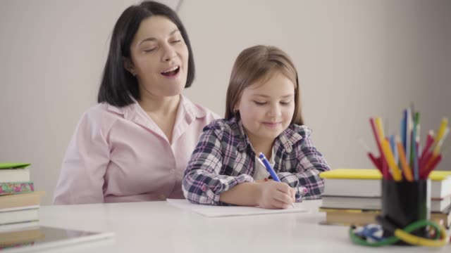 Portrait of cute Caucasian schoolgirl sitting with mom and writing in exercise book. Brunette mother helping daughter with homework. Support, education, studying.
