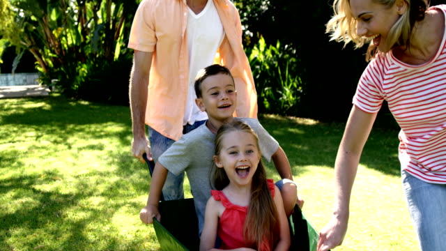 Portrait of cute family playing with the wheelbarrow in the garden video
