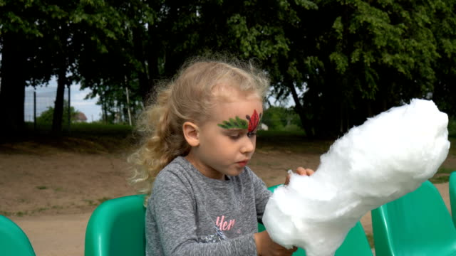 portrait of cute girl of 4 years, blonde, eats sweet white cotton candy. gimbal - lituania video stock e b–roll