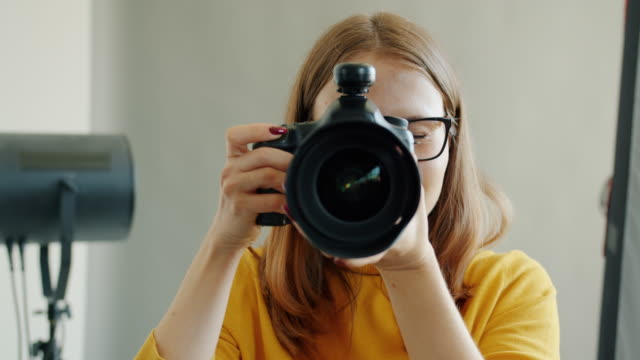Portrait of cute girl photographer taking picture then looking at camera smiling