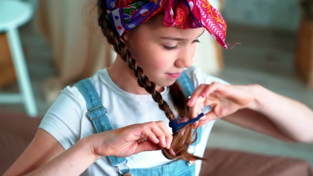 Portrait of cute girl ties braid with scrunchy and looks at camera, slow motion
