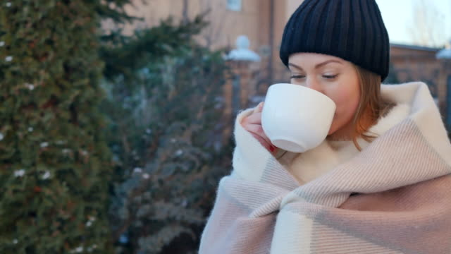Portrait of cute girl with red lips drinks a hot tea to warm at winter outdoors Charming young woman with red lips wrapped in a blanket is relaxing outdoors with cup of hot tea. Cute girl drinks a tea from a white cup and warms with beverage at winter. Beautiful female have a nice leisure time outdoors with hot tea. red lipstick stock videos & royalty-free footage