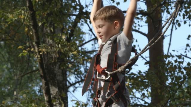 Portrait of cute little boy in an adventure rope park video