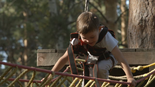 Portrait of cute little boy walks on a rope bridge in an adventure rope park video