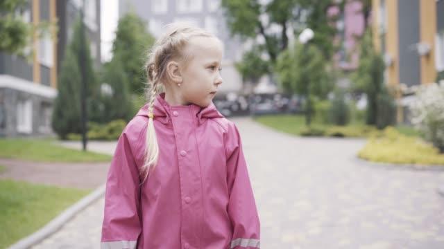 porträtt av söt liten flicka i vattentät kappa gå längs gränden utomhus. ganska kaukasiska barn i rosa kläder strosa på regnig dag. barndom, fritid, livsstil. - endast flickor bildbanksvideor och videomaterial från bakom kulisserna