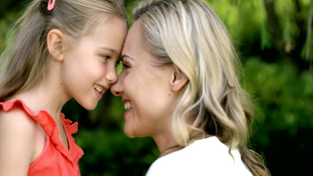 Portrait of cute mother and daughter embracing and smiling video