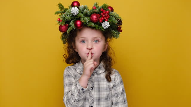 Portrait of cute preschool girl saying hush be quiet with finger on lips shhh gesture, wears handmade wreath, isolated on yellow background studio. Happy New Year celebration merry holiday concept