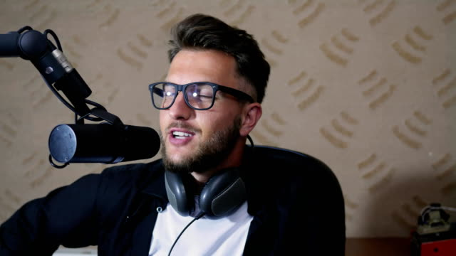 portrait of cute radio presenter into glasses speaks in microphone video
