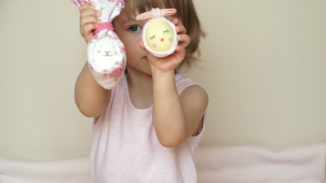 Portrait of cute smiling baby girl shows chicken eggs in hands, decorated for Easter bunny and chick, with painted muzzle.