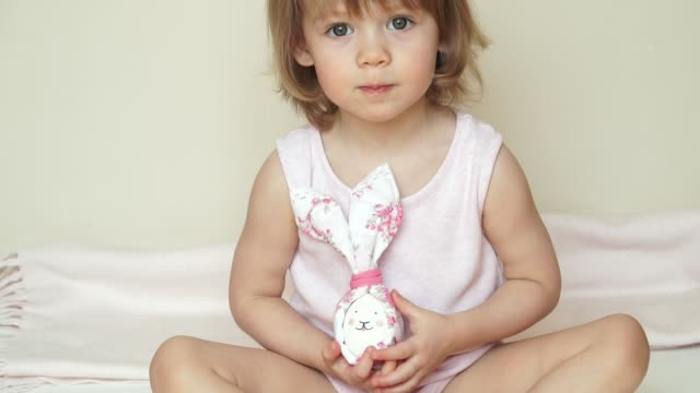Portrait of cute smiling baby girl sits and shows chicken eggs in hands, decorated for Easter bunny, with painted muzzle.