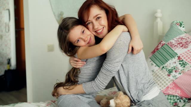 porträtt av söt leende flicka omfamnar hennes glada mor tittar kameran tillsammans medan du sitter på sängen i ljusa sovrum hemma - enbarnsfamilj bildbanksvideor och videomaterial från bakom kulisserna