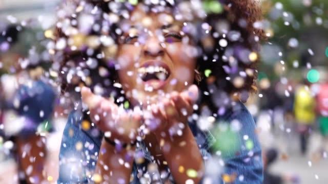 Portrait of cute woman blowing confetti video