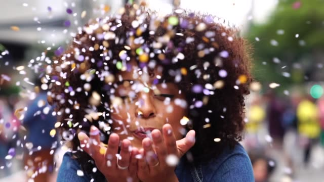 portrait of cute woman blowing confetti - goals filmów i materiałów b-roll