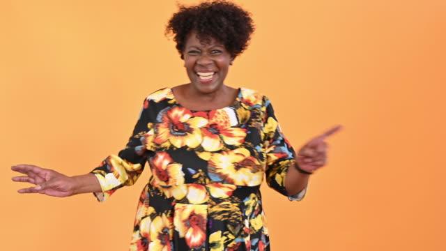 プリントドレスを着たダンスシニア黒人女性の肖像画 - disruptagingcollection点の映像素材/bロール