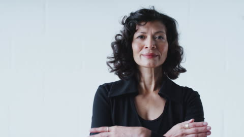 vídeos de stock e filmes b-roll de portrait of determined mature businesswoman in suit standing against white studio wall - fato
