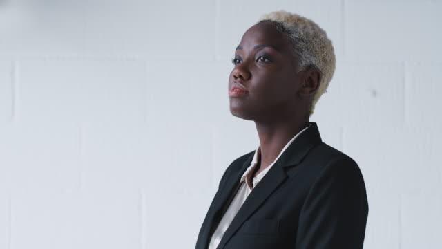 porträtt av beslutsamma unga affärskvinna bär kostym stående mot white studio wall - kostym sida bildbanksvideor och videomaterial från bakom kulisserna
