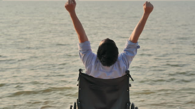 Portrait of disabled man raising hands outstretched on the beach in the wheelchair showing freedom.Success,Vacation,Travel,People,Insurance,Lifestyle,Leadership,business successful.The Disability Collection 2019.Traveling with Differing Abilities . video