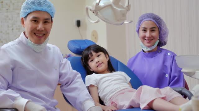 vídeos y material grabado en eventos de stock de retrato del dentista médico y niña en el consultorio del dentista, sonriendo, mirando a la cámara. linda niña sentada en la silla dental y teniendo tratamiento dental. medicina, estomatología y concepto de atención médica. chequeo dental, tecnologí - ortodoncista