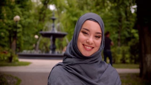 portrait of dreamy muslim student in hijab smiling into camera standing in front of the fountain. - abbigliamento religioso video stock e b–roll
