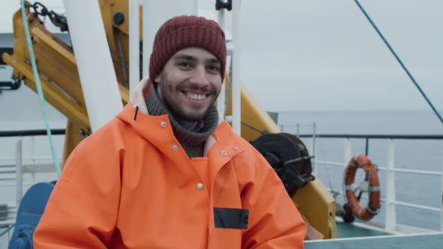 商業漁業のボートの漁師の笑みを浮かべての服を着て明るい保護コートの肖像画。 - 漁師 外人点の映像素材/bロール