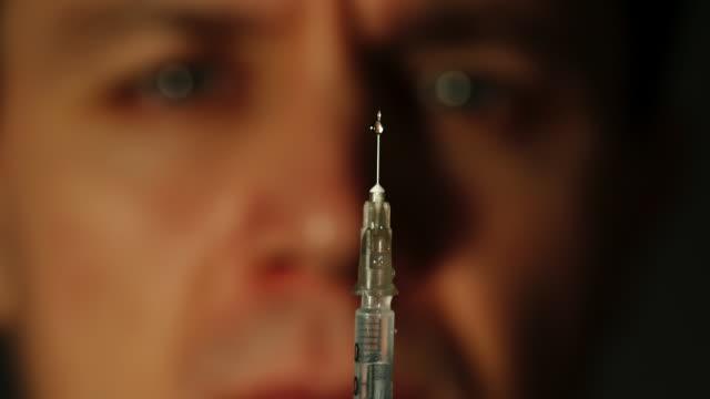 porträt von drogenabhängigen befasst sich mit der spritze - suchtkranker stock-videos und b-roll-filmmaterial