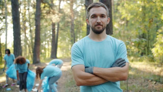 vídeos de stock, filmes e b-roll de retrato de homem ecológico voluntário em pé na floresta com os braços cruzados - voluntário