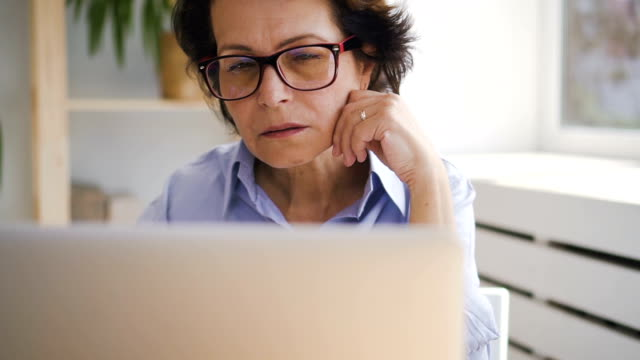 vídeos de stock e filmes b-roll de portrait of elderly business lady sitting in front of laptop screen at home - senior woman