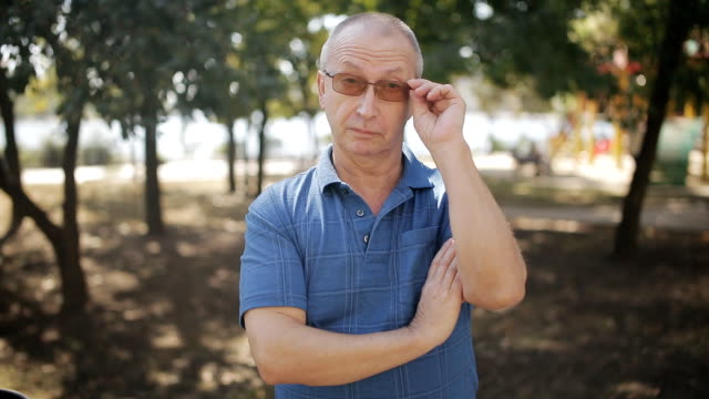 Portrait of elderly man with glasses in the Park looking at the camera