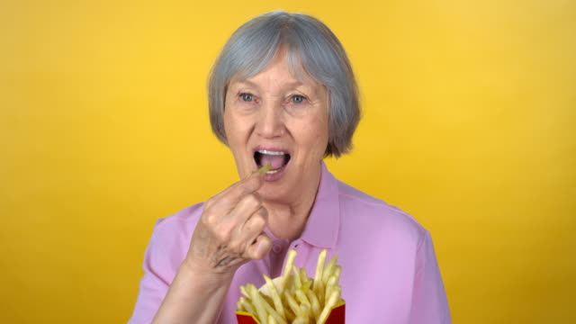 portrait of elderly woman eating fries - capelli grigi video stock e b–roll