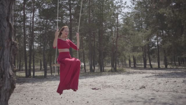 Portrait of elegant beautiful woman in red dress who sit in the forest on the swing. Portrait of elegant beautiful woman in red dress who sit in the forest on the swing and looking an amazing spectacular view. Beautiful nature. red lipstick stock videos & royalty-free footage