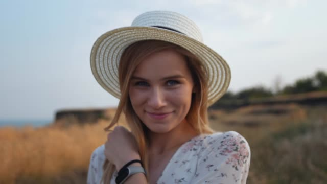 portrait of enchanting inspired girl in white dress with lovely smile walking on field. young woman in wicker hat walking down on meadow turning around and looking at camera. close up, slow motion. - figura femminile video stock e b–roll