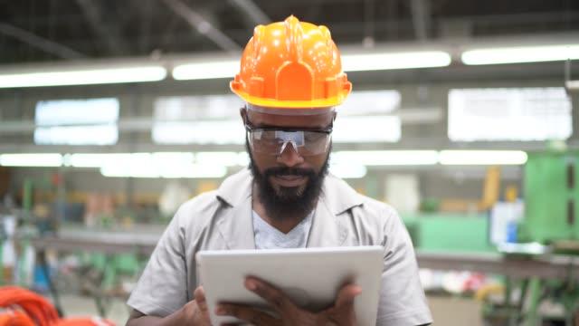 porträt des ingenieurs, der mit tablet in der fabrik arbeitet - arbeiter stock-videos und b-roll-filmmaterial