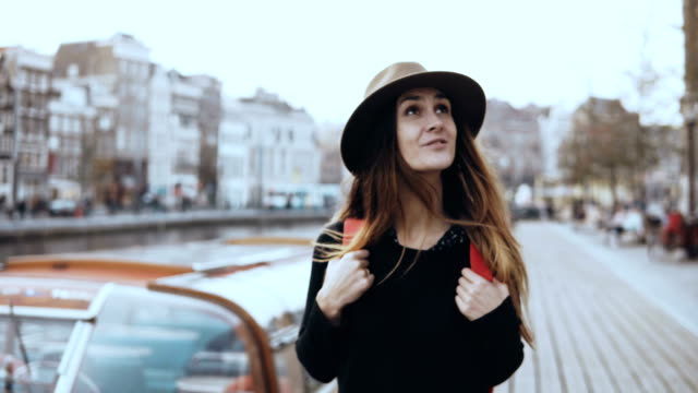 Portrait of European lady tourist walk near river. Happy thoughtful traveler female looks around on an embankment. 4K Portrait of European tourist walk near river. Happy thoughtful traveler female looks around on river boat embankment. Enjoying amazing city architecture scenery. 4K front view. Reflection and freedom. effortless stock videos & royalty-free footage