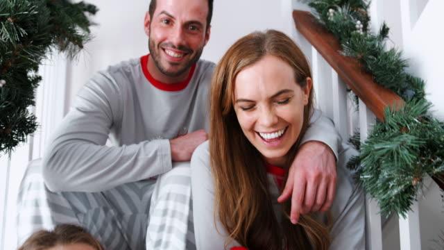stockvideo's en b-roll-footage met portret van opgewonden familie dragend pyjama's zitten op de trap op kerstochtend - christmas tree