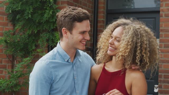 porträt von aufgeregten jungen paar stehen vor new home holding keys zusammen - hausschlüssel stock-videos und b-roll-filmmaterial