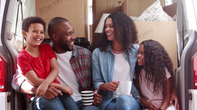 Portrait Of Family Sitting In Back Of Removal Truck On Moving Day video