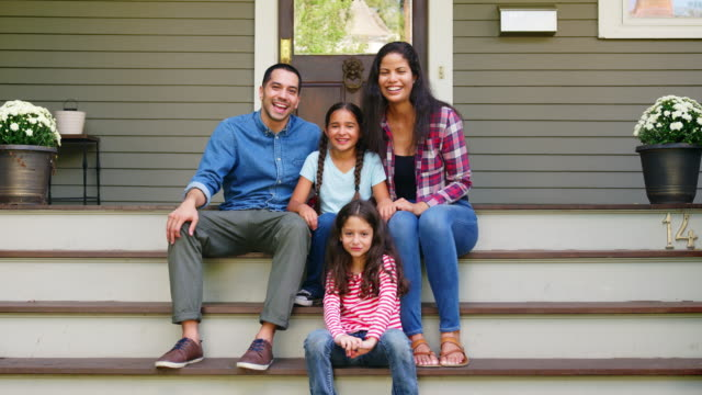 portrait of family sitting on steps in front of house - portico video stock e b–roll