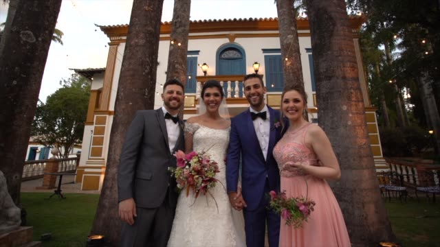 portrait of family taking a picture with the bride and groom - young couple wedding friends video stock e b–roll