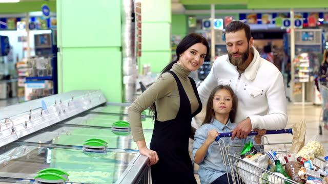 Portrait of family with a daughter near a large refrigerator in the supermarket.