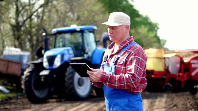 portrait of farmer or agronomist, in red plaid shirt, is typing in tablet smth, against background of tractors, agricultural machinery. modern agriculture, farming. warm sunny day - rancher video stock e b–roll