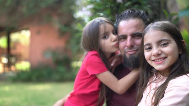 ritratto di padre e figlie sullo sfondo della casa - padre single video stock e b–roll