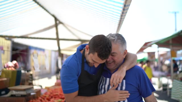 Portrait of father and son hugging while working in a street market Portrait of father and son hugging while working in a street market hug stock videos & royalty-free footage