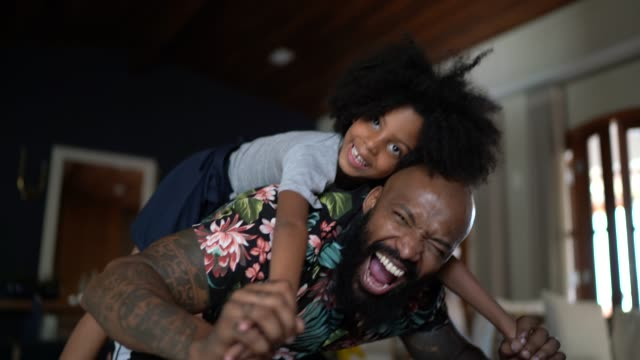 portrait of father giving his daughter a piggyback ride - parenting video stock e b–roll
