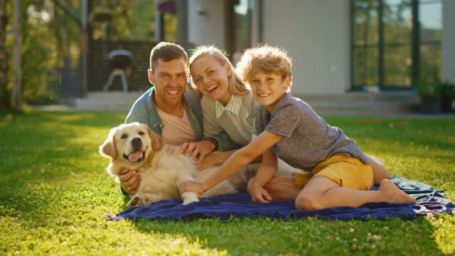 Portrait of Father, Mother, and Son Having Picnic on the Lawn, Posing with Happy Golden Retriever Dog. Idyllic Family Have Fun with Loyal Pedigree Doggy Outdoors in Summer House Backyard. Slow Motion