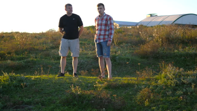 Portrait of father with his son talking outdoor at sunset. Two adult men are standing on green grass on the hill and speaking with each other. Father and son spend time together at nature in evening video