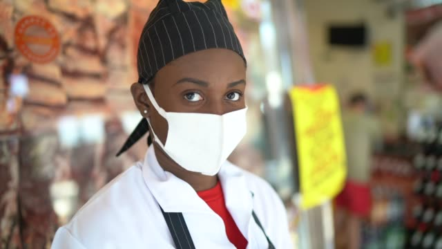 Portrait of female butcher working at butcher's shop - with face mask Portrait of female butcher working at butcher's shop - with face mask black people stock videos & royalty-free footage