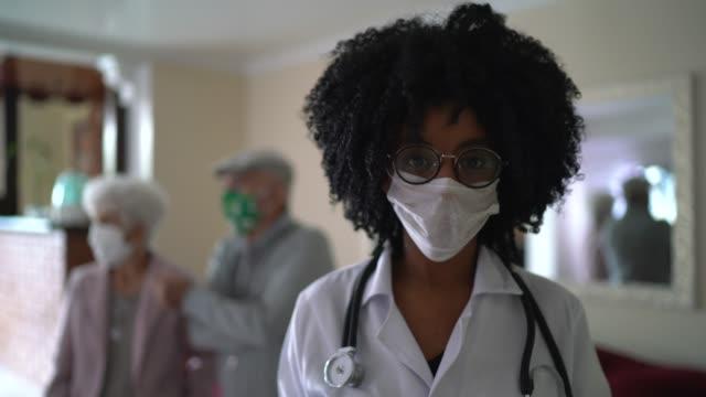 vídeos de stock e filmes b-roll de portrait of female doctor and a senior couple on background during home visit - enfermeira