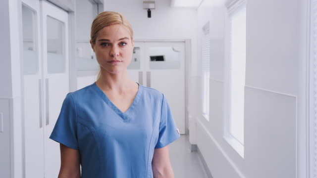 vídeos y material grabado en eventos de stock de retrato de una doctora que usa exfoliaciones en el pasillo del hospital - encuadre cintura para arriba
