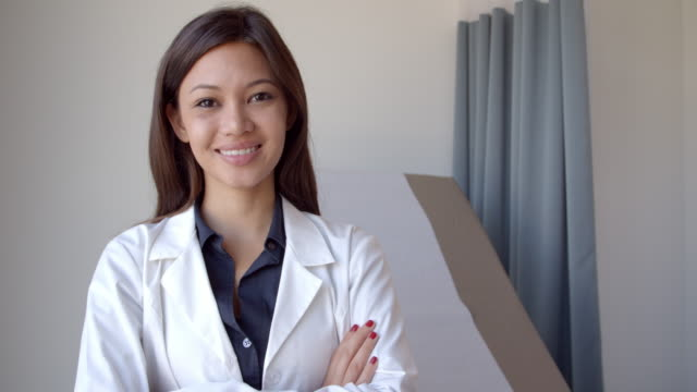 portrait of female doctor wearing white coat in exam room - doctor stock videos and b-roll footage