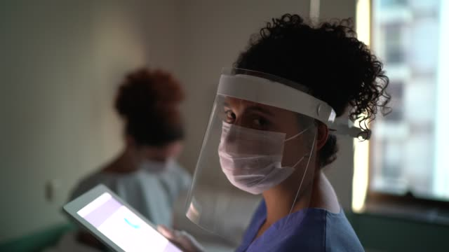 portrait of female doctor with face mask at hospital room - covid ospedale video stock e b–roll